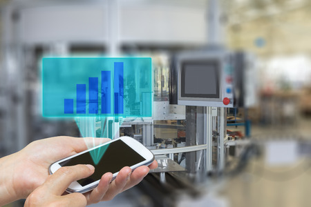 Female is using the smart phone Blank transparent rectangle with growth graph radiates from the screen pf  phone. The automatic production line is in the background. The edges of the pictures are deliberately blurred.
