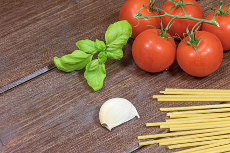 garlic cloves: Garlic cloves, basil leaves, spaghetti and tomatoes are lying on the wooden table.