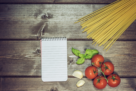 edited photo: Blank notebook with lined paper, garlic cloves, basil leaves, spaghetti and tomatoes are lying on the wooden table. Edited as a vintage photo with dark edges. Stock Photo