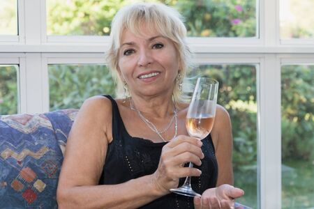 woman on couch: Senior mature blond woman is sitting on a couch and is smiling. She is holding a glass of champagne. Stock Photo