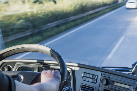 The driver is holding the steering wheel and is driving a truck on the highway. Free place for your text is in the right side of the photo. All potential trademarks are removed.