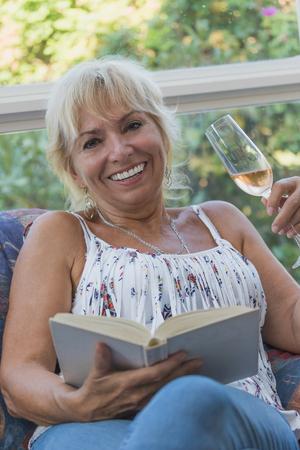 rubia: La mujer rubia sonriente maduro mayor est� sentado en un sof� y ella es la celebraci�n de una copa de champ�n en la mano izquierda y el libro en la mano derecha Foto de archivo