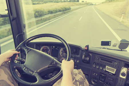 View on the dashboard of the truck driving. The driver is holding the steering wheel. Empty highway is in front of the car.   Zdjęcie Seryjne