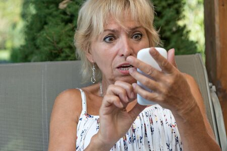 horrified: Blond senior woman is surprised to horrified from what she see in the smart phone, which is holding in her hand.