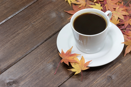 amarillo y negro: White cup of coffee and color maple leaves are in the upper right corner of photo. Foto de archivo