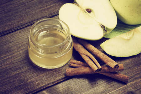 edited photo: Aerial view of a green apples sliced, a jar of honey and a cinnamon lying on a wooden table. Photo is edited as a vintage with dark edges. Stock Photo