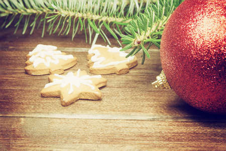 edited photo: Closeup view of the red Christmas bauble, branches of Christmas tree and Christmac gingerbread on the wooden desk. Photo is edited as a vintage photo with dark edges.