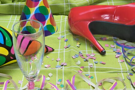 party popper: Closeup view of a green tablecloth after a party celebration with confetti, red court shoe and party popper. Champagne glass with lipstick imprint is in the foreground. All potential trademarks are removed.