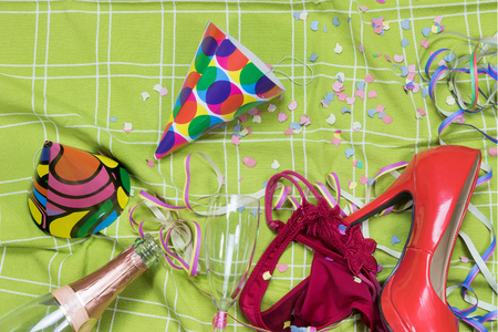 party popper: Shot of a green tablecloth after a party celebration with confetti, empty bottle, glass of champagne with lipstick imprint, party popper, red court shoe and rd panties.