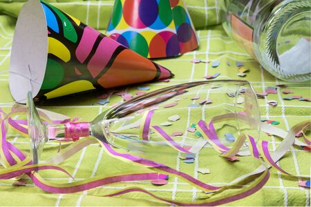 party popper: Closeup view of a green tablecloth after a party celebration with confetti, empty bottle and party popper. Champagne glass with lipstick imprint is lying in the foreground. All potential trademarks are removed.