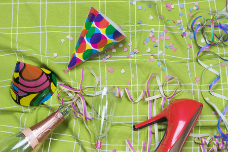 party popper: Shot of a green tablecloth after a party celebration with confetti, empty bottle and glass of champagne, party popper and red court shoe.