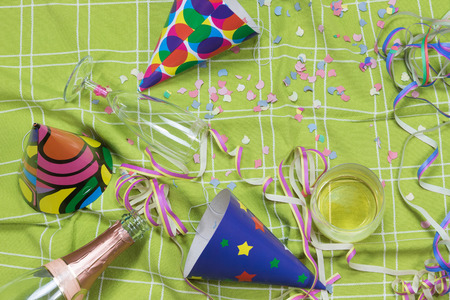 party poppers: Shot of a green tablecloth after a party celebration with confetti, empty bottle of champagne, champagne glass with lipstick imprint and party poppers