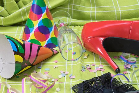 party popper: Shot of a green tablecloth after a party celebration with confetti, empty glass of champagne with lipstick imprint, party popper, red court shoe and black lace panties.