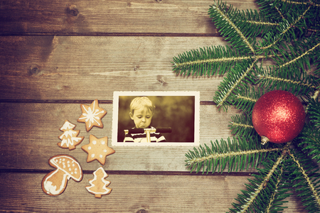 angry blonde: Vintage aerial view of the symbols of the Christmas on the wooden desk. The Christmas gingerbread is in the left side. On the old k  photo is disappointed and angry blonde boy standing on a scooter. Photo is edited as a vintage with dark edges.