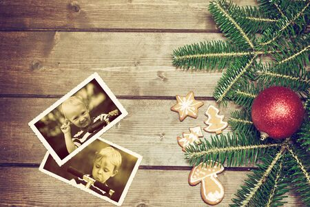 angry blonde: Vintage aerial view of the symbols of the Christmas on the wooden desk. The Christmas gingerbread is in the left side. On the two old k  photos is smiling blonde boy and angry blonde boy standing on a scooter. Photo is edited as a vintage with dark edges.