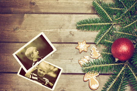 edited photo: Vintage aerial view of the symbols of the Christmas on the wooden desk. The Christmas gingerbread is in the left side. On the two old k  photos is smiling blonde boy and surprised blonde boy standing on a scooter. Photo is edited as a vintage with dark ed Stock Photo