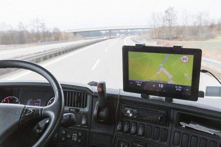 Inside the cab of the truck while driving. Focused on the tablet with navigation. The map is intentionally slightly out of focus. All potential trademarks are removed Stock Photo