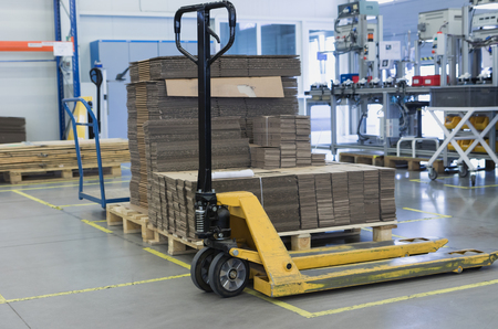 Pallet truck is standing in front of folded cardboard boxes in a designated place in the assembly hall. All potential trademarks are removed. Standard-Bild