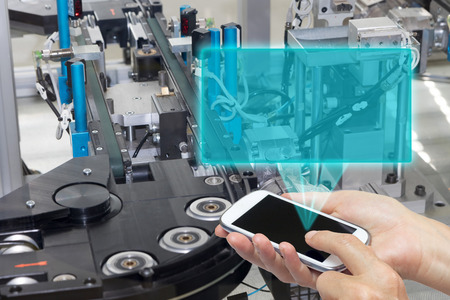 Female is holding the smart phone Blank transparent rectangle radiates from the screen smart phone. The rectangle is ready for your text. The automatic production line is in the background. All potential trademarks are rermoved.