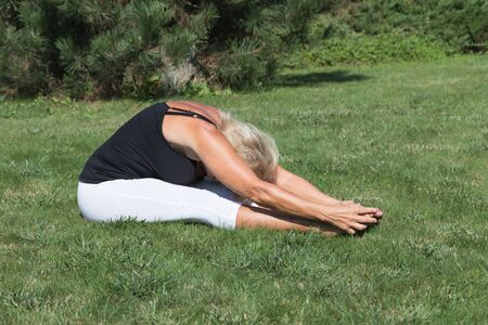 attractive female: Side view of flexible blonde senior woman stretching exercise outdoors. The woman is sitting forward bending on the lawn, her hands are holding the feets.