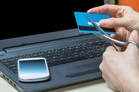e waste: Woman is sheering a credit card by scissors. White smart phone is lying on the dark notebook. All potential trademarks are removed. Stock Photo