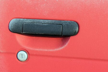 icy conditions: Frozen handle and lock of the red car closeup.