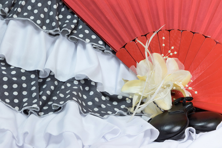 fan dance: Clothing for Flamenco dance in the color combination white and gray with white polka dots. The yellow  cloth rose, castanets and red fan are in the right side of the photo. Stock Photo
