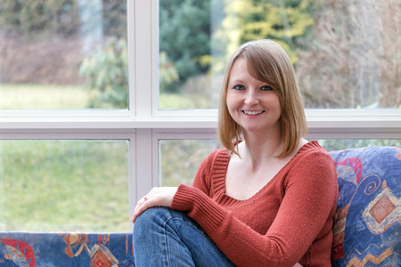 conservatory: Smiling young woman dressed in a brown sweater is sitting on the sofa in conservatory and she is looking at  the camera.