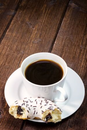 edited photo: Coffee cup is placed on a wooden board. The half of filled american donut is lying on the saucer. Photo is edited as an vintage with dark edges.