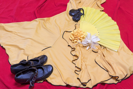 underlay: Yellow clothing for Flamenco dance. Black shoes, paper rose and castanets are lying on a red underlay. Stock Photo