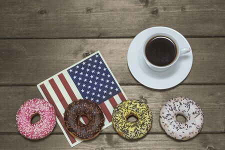 cup four: Four American donuts are lying in a row on the napkin in american flag design. Cup of coffee is lying on a wooden table upper. Edited as a vintage photo.