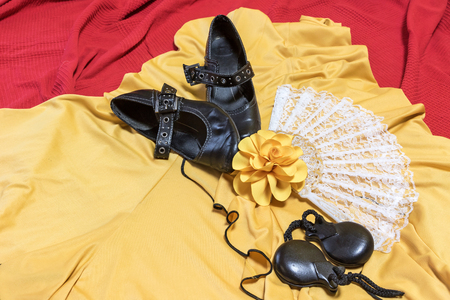 underlay: Aerial view of assesories for Flamenco dance. Black shoes, yellow rose, white fan and castanets are lying on a yellow clothes and red underlay.