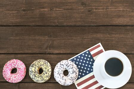 cup four: Four American donuts are lying in a row on a wooden table. Cup of coffee is lying on the napkin in american flag design.