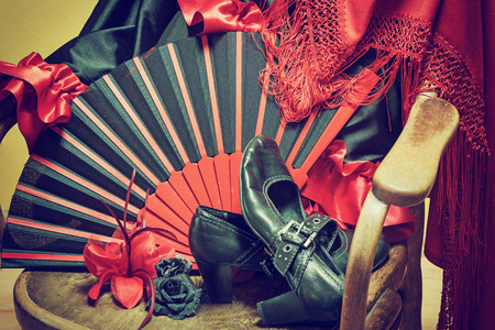 edited photo: Clothing for Flamenco dance. Black shoes, fan, red scarf with tassels and paper roses are lying on a vintage wooden chair. Edited as a vintage photo with dark edges.