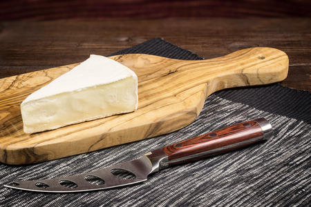 edited photo: Cheese with white mold it is lying on the board of olive wood. In a front of the cheese  on a tablecloth is lying stainless steel cheese knife with wood handle. Photo is edited as an vintage with dark edges.