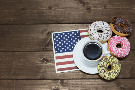 edited photo: Cup of coffee is lying on the napkin in american flag design. Four American donuts are lying around the cup of coffee. Edited a s a vintage photo. Stock Photo