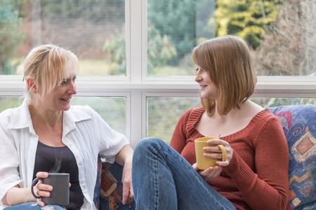 Midden oude vrouw en een jonge vrouw zijn samen chatten zittend op de bank in de serre.