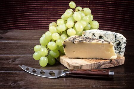 edited photo: Two kinds of cheese and grapes of the white wine are lying on the board of olive wood. Stainless steel cheese knife is lying on a wooden board in foreground. Photo is edited as an vintage with dark edges.