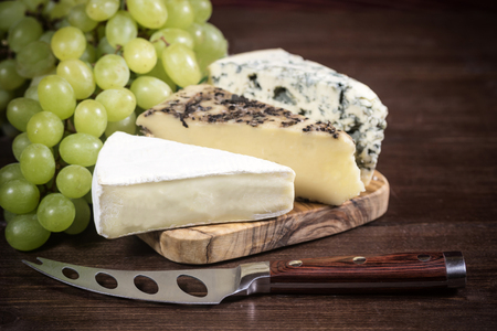 edited photo: Three kinds of cheese and grapes of the white wine are lying on the board of olive wood. Stainless steel cheese knife is lying on a wooden board in foreground. Photo is edited as an vintage with dark edges. Stock Photo