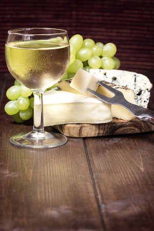 edited photo: Frosted glass with white wine, fresh grapes and different kinds of cheese with a fork are standing on a wooden table. Photo is edited as a vintage with dark edges. Stock Photo