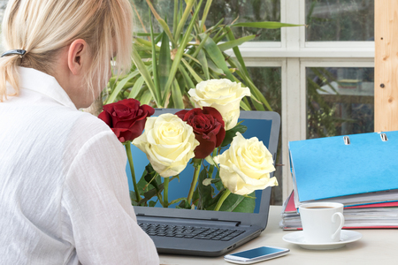 yelloow: Blond middle aged woman is sitting in the office. From the laptop is sticking out bouquet of red and yellow roses