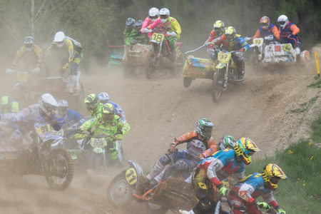 sidecar: MOHELNICE, CZECH REPUBLIC - APRIL 23. Group of sidecar racers in the dust after the start  in the Crossracing cup 2016- Sidecars Championship of Czech Republic on April 23. 2016 in Mohelnice.