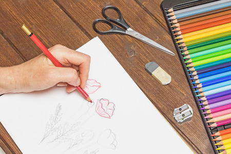 rubber sheet: Woman is relaxing by drawing a flowers with a red pencil on white paper. On the wooden table is ready set of multicolored crayons in a box, scissors, eraser and sharpener.
