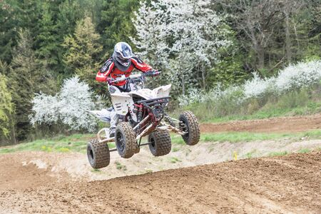 quad: MOHELNICE, CZECH REPUBLIC - APRIL 23. Quad rider in red is jumping  in the Crossracing cup 2016- Quad Championship of Czech Republic on April 23. 2016 in Mohelnice. Editorial