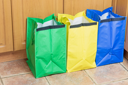 household waste: Green, blue and yellow bags are ready to use in sorting household waste Stock Photo