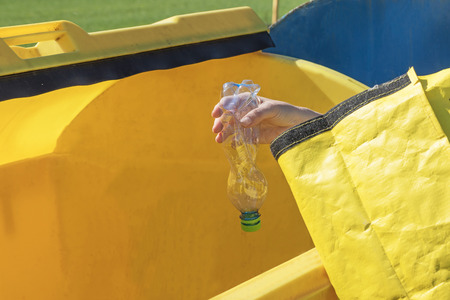 household waste: The woman is throwing a plastic bottle from yellow portable bag to yellow container for sorting plastic  household waste.