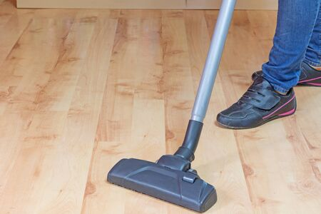 laminate flooring: Woman is cleaning laminate flooring by vacuum cleaner. Stock Photo