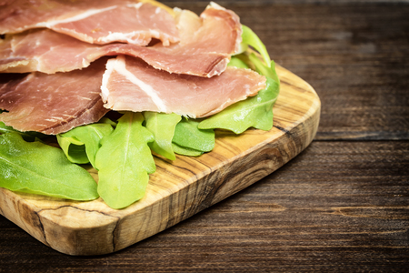 photo edges: Refreshments of sliced Spanish ham and arugula is lying on a wooden desk of olive tree. Edited as a vintage photo with dark edges. Horizontally. Stock Photo