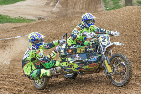 sidecar: MOHELNICE, CZECH REPUBLIC - APRIL 23. Closeup view of pair of the sidecar racers in the turn in the Crossracing cup 2016- Sidecars Championship of Czech Republic on April 23. 2016 in Mohelnice. Editorial