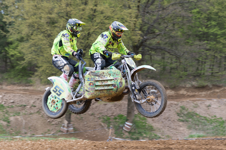 sidecar: MOHELNICE, CZECH REPUBLIC - APRIL 23. Sidecar racers are jumping in the turn in the Crossracing cup 2016- Sidecars Championship of Czech Republic on April 23. 2016 in Mohelnice.